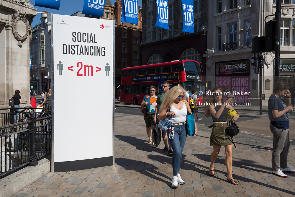 With a further 184 reported UK Covid deaths in the last 24 hrs, a total now of 43,414, shoppers pass through Oxford Circus where a post advises Londoners to observe the correct two metre social distances, during the Covid pandemnic lockdown, now easing after three months of the Stay At Home policy but now being relaxed as the shops re-open, on 26th June 2020, in London, England. Government restrictions on the 2 metre rule is to be realxed on 4th July and replaced with 'one metre plus' in the hope it stimulates the struggling UK economy.