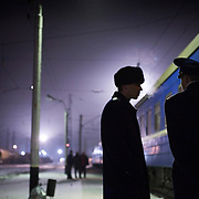 Conductors chat as their night train makes a stop in Perm in central Russia. The train, beginning in Berlin, Germany, goes through Poland and Belarus, and ends in Irkutsk, Russia. The entire journey takes six days.