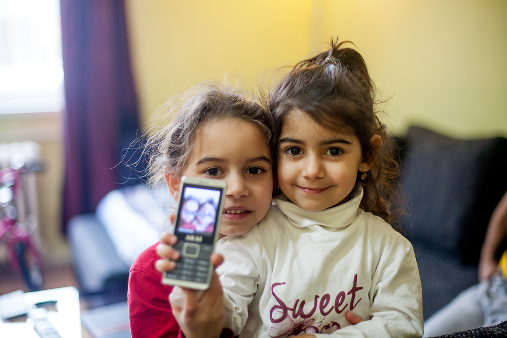 """Sara (6) on the left and Kristina (4) with a mobile phone they used to tak photograhs in their temporary home in Ostrava. Sara's mother was advised from one of the schools that she should not enrol her daughter there - after the girl passed the enrolment test - because Sara is so """"slim"""". Mother Ingrid Kandracova (36) new that the final decision is on her side and she refused the advice and enrolled her daughter in the school."""