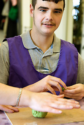 Day Service user with learning disabilities in an arts and craft session,