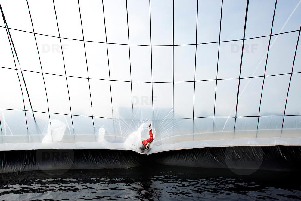 Nederland Delft 30 augustus 2007 20070830..Pino Ciampienetti tel 070 3656368, medewerker organisatie, Pino Ciampienetti tel 070 3656368, medewerker organisatie waterpiramide, verlaat de waterpiramide door door een sleuf naar buiten te glijden ..Waterpiramide op zonne-energie.Langs de A13 bij Delft is vanaf donderdag een piramide te zien die water zuivert op zonne-energie. Het bijna negen meter hoge bouwwerk wordt normaal gesproken in ontwikkelingslanden opgebouwd om zout en vervuild water te destilleren..?.De bedenker, ingenieur Martijn Nitzsche, demonstreert zijn uitvinding deze maand wegens het lustrum van de TU Delft. ..De waterpiramide is een grote witte tent met een grondoppervlakte van zo'n 650 vierkante meter, die vooral in de tropen, nabij de kust, wordt ingezet. Het zoute water dat in de piramide wordt gepompt, verdampt als overdag de zon op het doek schijnt en de lucht in de tent tot zo'n 75 graden oploopt. Het vuil en het zout blijven op de grond achter en het schone, zoete water druppelt langs de binnenkant van het doek om in een gootje te worden opgevangen. Per dag wordt op deze manier zo'n 1500 liter gegenereerd, dit water kan via jerrycans naar de verschillende dorpen in de omgeving worden gebracht.  ..,,In Afrika staan nu twee van deze tenten. Binnenkort komen er nog vier in Azië bij'', aldus Nitzsche. De Wereldbank beloonde de Delftse ingenieur in 2006 met de innovatieprijs van 190 duizend dollar voor zijn uitvinding. ..Aanvullende info: www.waterpyramid.nl.The need?.?.The need for safe, clean drinking water is increasing rapidly. Natural supplies can no longer cope, and shortages happen around the world - especially in tropical and developing counties. There is often enough water available, but it is salty, brackish or dirty, and needs cleaning to make it safe to drink.??Governments, scientists and engineers are working on .?.ways to do this, but existing methods such as 'multi flash distillation' or 'reverse osmosis' have many drawbacks. The equip