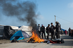 October 23, 2016 - Calais, France - Migrants burn on a road in the Calais Jungle in Calais, France, on 23 October 2016, before the upcoming evacuating sleeping bags and camping mats. The refugee camp on the coast to the English Channel is to be cleared on monday, according to the French government. The approximately 8,000 refugees are distributed to various reception centers in France. (Credit Image: © Markus Heine/NurPhoto via ZUMA Press)