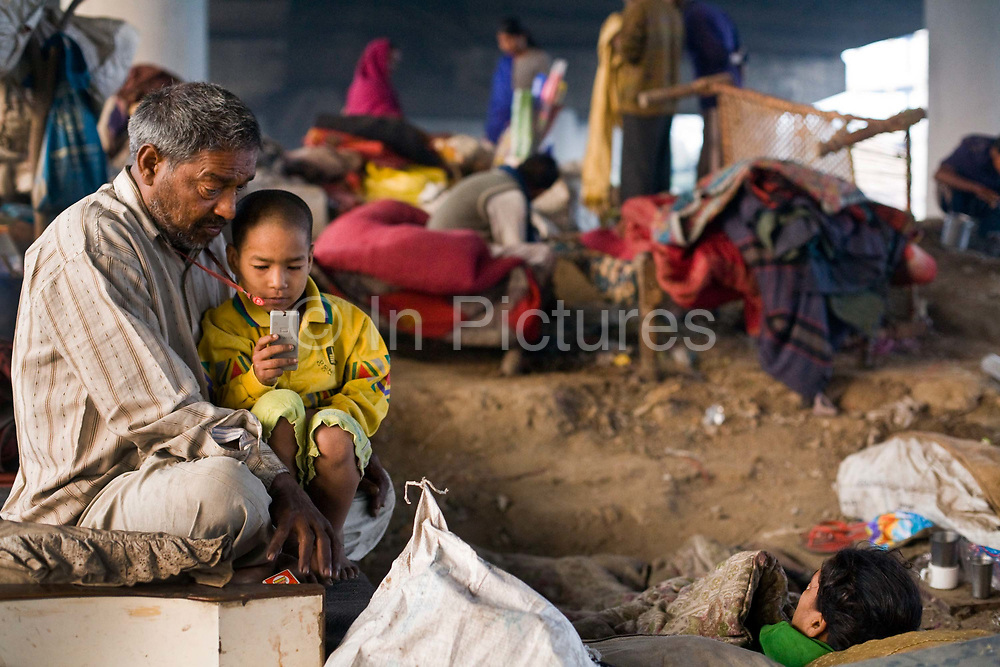 Ram Pal Gupta, a ballon seller that lives beneath a bridge next to railway tracks in Okhla sits with his youngest daughter, Jyoti (6). Gupta has lived here with his wife who has mental health issues for seven years.