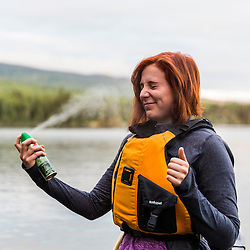 A woman applies some bug spray before a morning paddle on Long Pond in Maine's north woods. At the Appalachian Mountain Club's Gorman Chairback Lodge. Near Greenville, Maine.