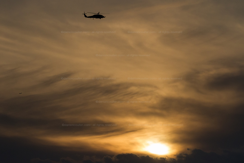 A silhouette of a US Navy Sikorsky SH-60R Seahawk helicopter with the the Maritime Strike Squadron 51 against a cloudy, sunset sky near Naval Air Facility,, Atsugi airbase in Kanagawa, Japan. Thursday February 25th 2021