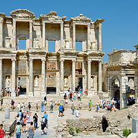 The reconstructed Library of Celsus which is the ancient city's most famous building. Turkey. Ephesus. It was built in AD 114 – 117 by Consul Gaius Julius Aquila as a mausoleum for his father, Julius Celsus Polemaeanus, who is buried in a in a tomb under the apsidal wall on the right side of the back wall. The library was one of the wealthiest in the empire and at its peak had more than 12,000 scrolls. The statutes seen in the niches between the doors symbolized wisdom, Sophia, Knowledge (episteme), intelligence (ennoia) and virtue (arte) of Celsus.