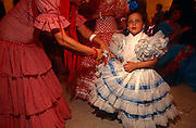 A mother attends to her young flamenco-dressed daughter in a caseta (marquee) during the Spring Feria in Seville. ..It is a lively event that Seville holds annually in the vast fairground area on the far bank of the Guadalquivir River. Rows of temporary marquee casetas, host families, corporations and friends into the late hours during the April Fair which begins begins two weeks after the Semana Santa, or Easter Holy Week in the Andalusian capital.