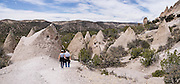"""See fantastic hoodoos and a great slot canyon in Kasha-Katuwe Tent Rocks National Monument, in New Mexico, USA. Hike the easy Cave Loop Trail plus Slot Canyon Trail side trip (3 miles round trip), 40 miles southwest of Santa Fe, on the Pajarito Plateau. Distinctive cone-shaped caprocks protect soft pumice and tuff beneath. Geologically, the Tent Rocks are made of Peralta Tuff, formed from volcanic ash, pumice, and pyroclastic debris deposited over 1000 feet thick from the Jemez Volcanic Field, 7 million years ago. Kasha-Katuwe means """"white cliffs"""" in the Pueblo language Keresan. This panorama was stitched from 2 overlapping photos."""