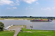 Nederland, Varik, 9-6-2018Een binnenvaartschip vaart over de Waal beladen met containers richting Duitsland .In dit deel van de Waal zijn de kribben verlaagd of vervangen door langsliggende dammen om de waterafvoer te verbeteren . Op de voorgraond een camperplaats waar toeristen, dagjesmensen, met hun camper mogen staan .Foto: Flip Franssen