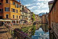 View of The French Alps, and colorful buildings taken from a bridge above the reflective waters of Thiou Canal, Old Town Annecy, France.