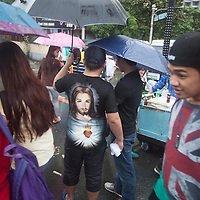 Religious T-shirts were worn by many people. Despite it raining all day, between six and seven million people turned out for a mass by Pope Francis in Rizal Park in Manila.