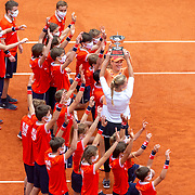 PARIS, FRANCE October 11.  Tímea Babos of Hungary and Kristina Mladenovic of France celebrate with the ball boys and girls after their victory against Alexa Guarachi of Chile and Desirae Krawczyk of the United States in the Women's Doubles Final on Court Philippe-Chatrier during the French Open Tennis Tournament at Roland Garros on October 11th 2020 in Paris, France. (Photo by Tim Clayton/Corbis via Getty Images)
