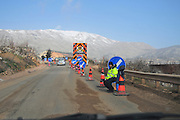 Israel, Golan Heights, Road works the snow covered Hermon mountain in the background