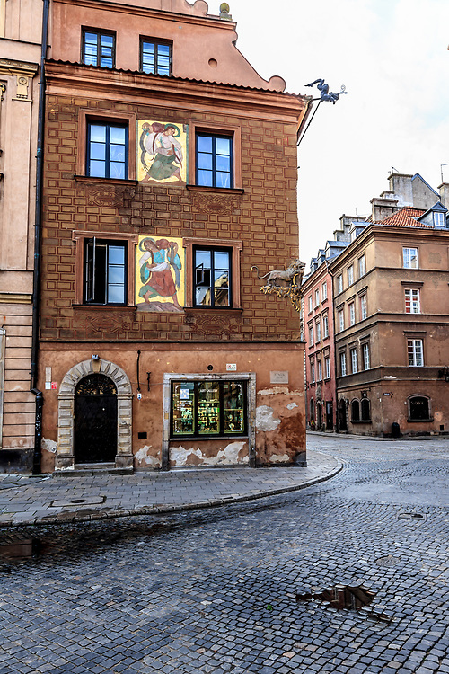 """""""Pod Lwem"""" house on Old Town Square in Warsaw, Poland. """"Pod Lwem"""" house in Warsaw, Poland has an original late Renaissance gable, a relief of a lion, coming from around the half of the XVIII century, and a polychromy of Zofia Stryjeńska, the only one that remained of a complex of the Old Town polychromies created in 1928 - 1929."""