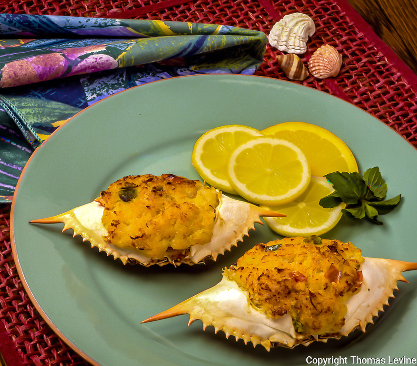 Stuffed crab with lemon on a blue plate with red table mat and seashells for decoration.