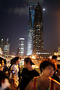Pedestrians walk past the World Financial Center (Left) and Jinmao Tower (Right) in Shanghai, China on 19 October 2010. Shanghai, China's largest city, is quickly becoming one of the major financial centers of the world.