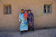 Mongolian Shepherd Manduhu, right, with his brother in law and his sisters son, in front of his house, Inner Mongolia, China