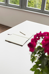 Notebook and roses on table