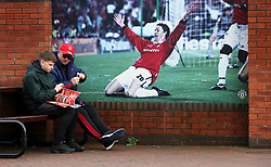 Fans sit next to a picture of new Manchester United interim manager Ole Gunnar Solskjaer outside the ground ahead of the Premier League match at Old Trafford, Manchester.
