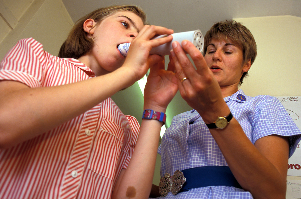 Practice nurse monitoring  young girl with asthma,