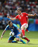 Gareth Bale of Wales ® is challenged by Juraj Kucka of Slovakia. Euro 2016, Wales v Slovakia at Matmut Atlantique , Nouveau Stade de Bordeaux  in Bordeaux, France on Saturday 11th June 2016, pic by  Andrew Orchard, Andrew Orchard sports photography.