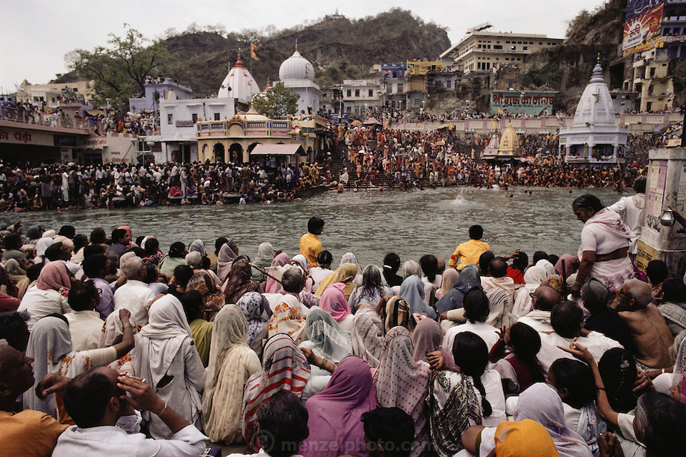 Every 12 years, millions of devout Hindus celebrate the month-long festival of Kumbh Mela by bathing in the holy waters of the Ganges at Hardiwar, India. Hundreds of ashrams set up dusty, sprawling camps that stretch for miles. Under the watchful eye of police and lifeguards, the faithful throng to bathe in the river. Here, across the river, a ghat is dedicated to sadhus and nagas so they can bathe in relative peace.