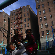 Children play in a playground in the Bronx near Yankee Stadium before the New York Yankees V Baltimore Orioles American League Division Series play-off decider at Yankee Stadium, The Bronx, New York. 12th October 2012. Photo Tim Clayton