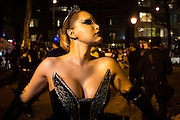 New York, NY - 31 October 2016. A woman in a winged bustier and a fishnet mask poses before the Greenwich Village Halloween Parade.