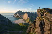 Female hiker takes in view over Bunes beach from isolated mountain peak, Moskenesøy, Lofoten Islands, Norway