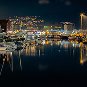 www.aziznasutiphotography.com                                History:<br /> The Trondheim canal, or rather canal harbour, was built during the 1870ies and was ready for use in 1884. It was built by raising the sandbanks utside town and building quays and railroad station on this articifially built island. The whole area is an island.<br /> The quays at the seaside were built for ships going overseas and the quays on the town side for local ships. Between these quays a new central railway station for Trondheim was built.<br /> When the railroad was changed from narrow gauge to normal gauge a lifting bridge was built at Skansen at the western part och the canal. This bridge was opened for traffic in 1918, and is the only lifting bridge for railroads in Norway that is still used.<br /> In the eastern part of the canal there are to two lifting bridges for cars, but they are not in use any longer.<br /> The canal has one further connection to the sea, the Ravnkloa canal. It runs from the midst of the canal out to the sea. There's a fixed bridge crossing the canal. Small sightseeingboats to the old castle Munkholmen use this canal in the sumnmer.