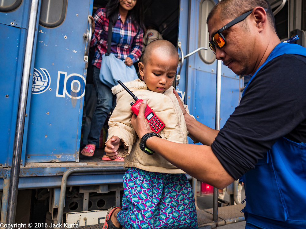 26 OCTOBER 2016 - MAE SOT, TAK, THAILAND:  An IOM (International Organization for Migration) official helps Burmese children off the bus that brought them to the border in Mae Sot for their repatriation from the Nupo Temporary Shelter refugee camp. Sixtyfive Burmese refugees living in the Nupo Temporary Shelter refugee camp in Tak Province of Thailand were voluntarily repatriated to Myanmar. About 11,000 people live in the camp. The repatriation was the first large scale repatriation of Myanmar refugees living in Thailand. Government officials on both sides of the Thai / Myanmar border said the repatriation was made possible by recent democratic reforms in Myanmar. There are approximately 150,000 Burmese refugees living in camps along the Thai / Myanmar border. The Thai government has expressed interest several times in the last two years in starting the process of repatriating the refugees.     PHOTO BY JACK KURTZ
