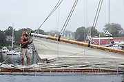 A deckhand furls the mainsail aboard the windjammer schooner Appledore II at the dock in Camden, Maine.