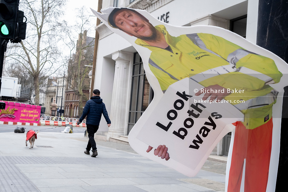 A dog walker passes a construction industry warning sign, erected to warn pedestrians, but damaged so that it is seemingly bending over at the waist, on 8th March 2021, in London, England.