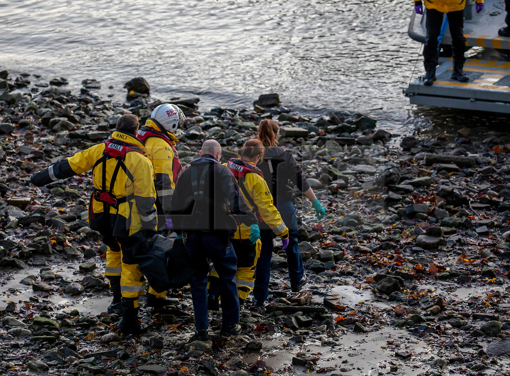 © Licensed to London News Pictures. 29/11/2019. London, UK. RNLI and Ambulance  crews remove a body of an unidentified person from the beach on the north side of Vauxhall Bridge. Emergency crews responded earlier to an incident underneath Vauxhall Bridge during this morning's rush hour where a body of an unidentified person was found. Photo credit: Alex Lentati/LNP