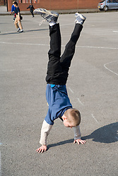 Young boy doing handstand in school playground,
