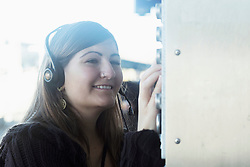 Young woman wearing headset and controlling switch, Freiburg im Breisgau, Baden-Württemberg, Germany