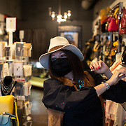 """CHARLOTTE NC - MAY 8: Linda Martinez, an employee at CLTCH, a clothing and accessory shop in the Plaza Midwood neighborhood straightens up jewerly on a shelf inside the shop in Charlotte, NC on May 8, 2020. Commercial businesses that were deemed """"non-essential"""" are able to reopen at 5pm on May 8th under North Carolina Governor, Roy Cooper's phase 1 plan to reopen the state economy. (Logan Cyrus/ Bloomberg )"""