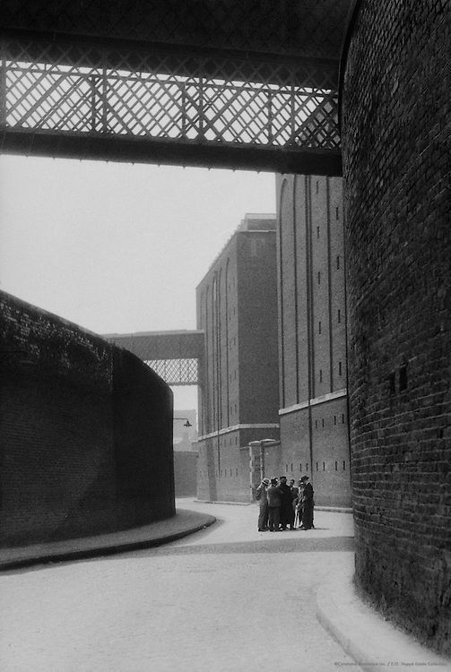 Group on a Street Surrounded by Brick Walls, London, England, 1933