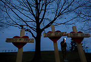 Greg Zanis stands among some of the 129 wooden crosses that he built as a vigil, each bearing the name of one of the murder victims in Chicago, at Northern Illinois University in DeKalb, Illinois.  Photo by Jim Young