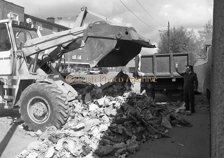 Army Removes Refuse In Dublin..1986..05.06.1986..06.05.1986..5th June 1986..Due to the ongoing strike by Dublin Corporation workers,the army were called in to help clear some of the mounds of rubbish stacking up around the city. Health worries from the rotting rubbish and the danger of rat infestation caused the intervention. The 2nd Garrison Supply and Transport Company,McKee Barracks,Dublin were delegated to clear the rubbish from St Theresa's Flats,Donore Avenue,Dublin...Picture shows soldiers operating the bulldozer to clear some of the rubbish building up around the city. Here the sergeant directs the operation.