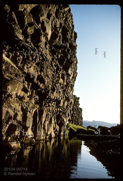 Rock wall towers over pool in Almannagja rift @ Thingvellir, 1st site of world's oldest parliamnt Iceland