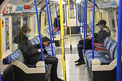 © Licensed to London News Pictures. 20/03/2020. London, UK. Passengers wearing masks observe social distancing. London's underground network that at its peak handles 5 million passenger journeys a day was left all but abandoned on Friday night as the coronavirus outbreak escalated. This latest phase of social distancing follows as the government announced the immediate closure of bars, pubs and restaurants to reduce person to person contact and virus transmission. Photo credit: Guilhem Baker/LNP