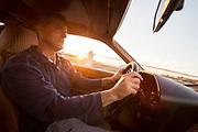 Image of a man driving a Porsche 928 at sunset, Balboa Island Bridge, California, America west coast by Randy Wells