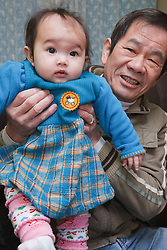 Portrait of grandfather with baby granddaughter.