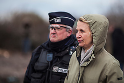 © Licensed to London News Pictures. Calais, France. 02/03/16. With a police escort, Calais Prefect Fabienne Buccio (right) surveys progress made on the third day of the demolition of the Calais 'Jungle' camp. French authorities have begun clearing the southern half of the camp, which charities estimate to contain some 3,500 people. Photo credit: Rob Pinney/LNP