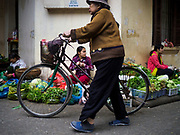 "22 DECEMBER 2017 - HANOI, VIETNAM: A woman pushes her bike past vegetable sellers in a market in the old quarter of Hanoi. The old quarter is the heart of Hanoi, with narrow streets and lots of small shops but it's being ""gentrified"" because of tourism and some of the shops are being turned into hotels and cafes for tourists and wealthy Vietnamese.    PHOTO BY JACK KURTZ"