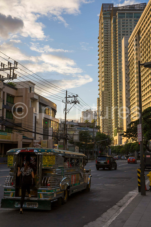 A jeepney stops on the side of the road in attempt to get customers on Antonio Arnaiz Ave, Makati, Metro Manila, Philippines. A jeepney, or 'dyipni' in Filipino, is a repurposed military jeep that is used as a free taxi in the Philippines. The high-rise building in the background is the Park Terraces building.