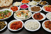 A dish of Humus surrounded by dishes other local salads such as eggplant, olives green salad and hot peppers usually served with pita as a mezze in middle eastern restaurants in Israel