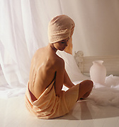 Rear view of woman sitting in stylized bathroom set with towel wrapped on head and around hips illuminated by natural light