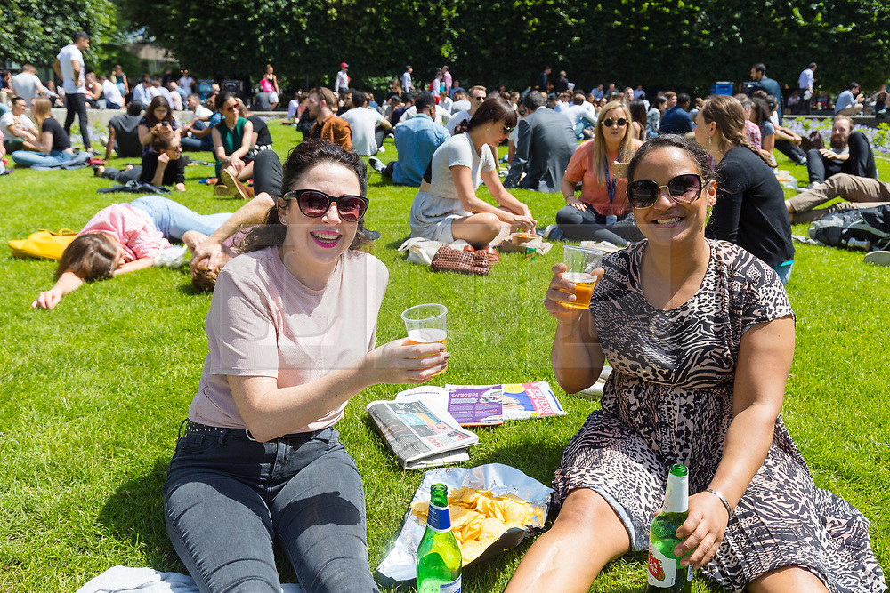 © Licensed to London News Pictures. 28/06/2019. London, UK.  Diane and Natasha enjoy a picnic lunch and drink during warm and sunny weather near St Paul's Cathedral in London on Friday lunchtime. A heatwave is forecast across much of the UK tomorrow, with temperatures in the capital expected to reach 33 degrees celcius.  Photo credit: Vickie Flores/LNP